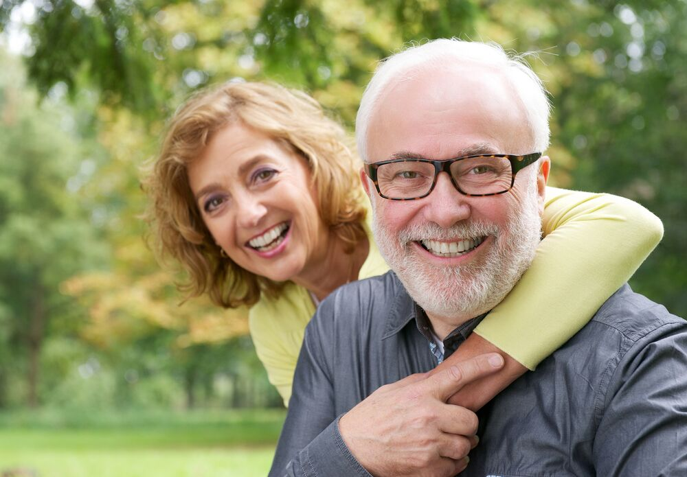 older couple smiling in front of tree